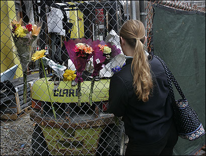 An unidentified co-worker of the doctor who was killed placed flowers on a memorial on a fence at the construction site.
