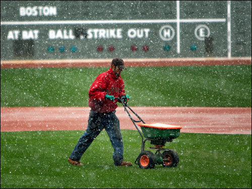 With Opening Day at Fenway Park just days away, heavy snow fell at 11:15 a.m. on Wednesday, as a member of the Fenway grounds crew used a spreader on the infield.