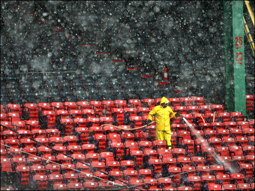Heavy snow fell as Eliezer Cepeda, a facilities worker at the park, used a hose to wash the left field seats.