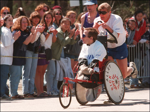 Dick Hoyt and his son Rick, from Holland, Mass., passed the crowd at Wellesley College during the 100th running of the Boston Marathon in 1996.