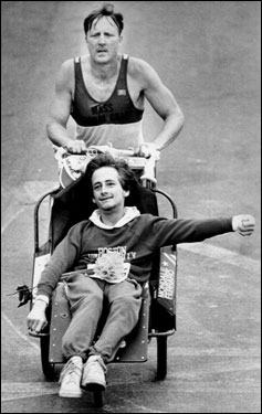 Rick was born with cerebral palsy, which has confined him to a wheelchair for the rest of his life. It was Rick who got the idea to start racing from an article about a crash victim who raced after being paralyzed. His dream came to fruition in 1981, the first time Team Hoyt ran the Boston Marathon. They are pictured here in their fifth year of participation.