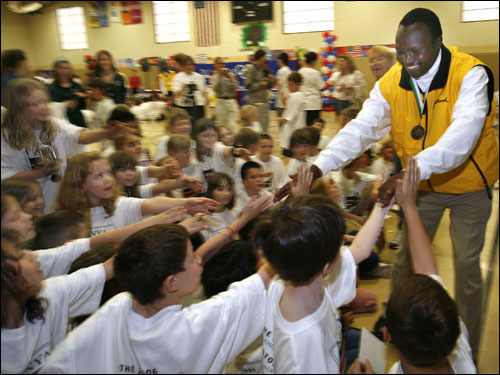 Moses Tanui, who won the Boston Marathon in 1996 and 1998, shook hands with students at the Elmwood Elementary School in Hopkinton after answering their questions.