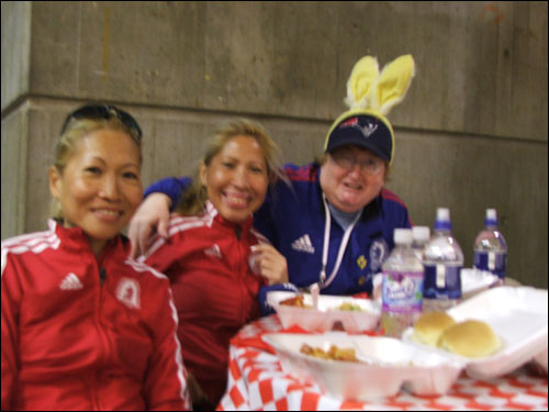 Race volunteer Mary-Ann Connors (right) posed with some runners who were enjoying their pasta dinner. Connors has been a volunteer for 16 years.