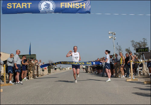 Navy Lt. Cmdr. Matt Simms crosses the finish line with a time of 2 hours, 53 minutes, 35 seconds to win the men's race. Commander Simms is currently based at Camp Slayer in Baghdad.