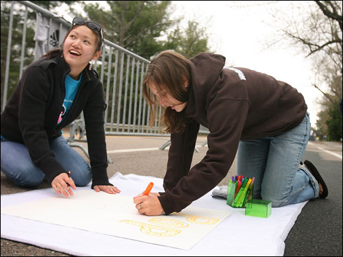 Stephanie Chan (left) and Claire Marana made a 'pop a wheelie' sign for the wheelchair racers in the marathon.