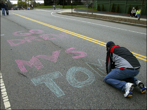 Scot Martel of Methuen wrote encouraging messages on Heartbreak Hill for friends running the Boston Marathon on Commonwealth Ave.