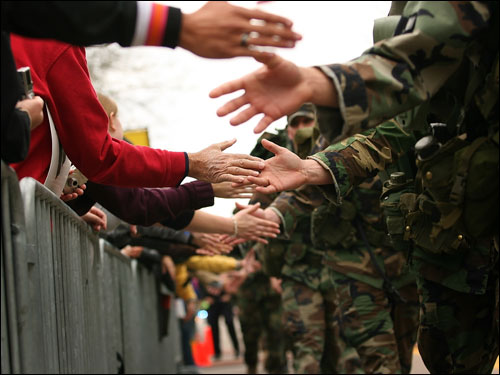 Supporters slapped the hands of National Guardsmen walking the marathon route in Wellesley.