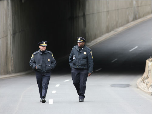 Boston Police officers, Lt. Colm Lyden (left) and Sgt. Steve Downs, walked the marathon route under the Massachusetts Avenue Bridge on Commonwealth Avenue before the racers arrive.