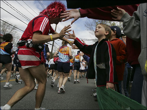 This is a look at the colorful and exuberant scene at the starting line of the 110th running of the Boston Marathon. Six-year-old Jonathan Katz of Hopkinton got a high five from one of the funkier runners.