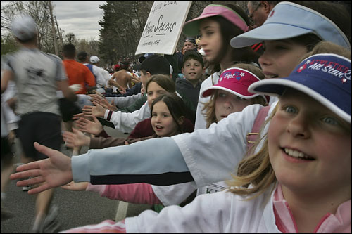 Hopkinton 9-year-olds Anna Charteris, and next to her in the blue visor Madeline Boyce, cheered on the runners near the starting line of the Boston Marathon.