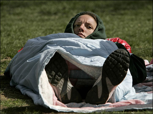 Keeping as warm as possible in the cool morning air on the Hopkinton Green was Tracy Weitthoff of Ohio. She rested before running her second Boston Marathon.
