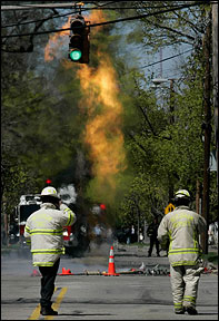 Firefighters watch a blaze from a gas line at the intersection of Webster Street and Harris Avenue in Needham.