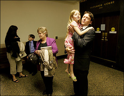Mark Petrie, whose wife died after giving birth at Newton-Wellesley Hospital nine years ago, greeted his daughter, Alexandrea, in Suffolk Superior Court yesterday. At center, his late wife's mother, Marianne Coates of New York, and his son, Cameron.