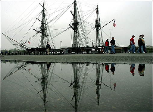 Heavy fog obscured the Boston skyline as it contrasted with the masts of the USS Constitution, clearly reflected in a puddle.