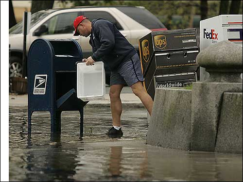 postal worker collects mail despite flood