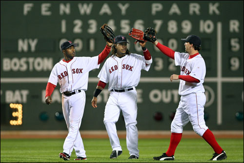 Red Sox outfielders (left to right) Willie Harris, Manny Ramirez, and Trot Nixon high five after the final out of Boston's 9-5 victory over the Yankees at Fenway Park.