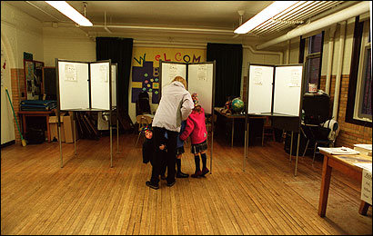 Boston plans a drive to boost voter turnout that would allow same-day registration. Above, a voter and her children in Hyde Park.