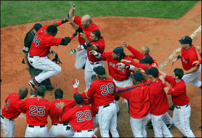 Red Sox teammates mob David Ortiz (No. 34) as he arrives at home plate after his walkoff home run gave Boston the 5-4 victory over Texas in the opener of their doubleheader.
