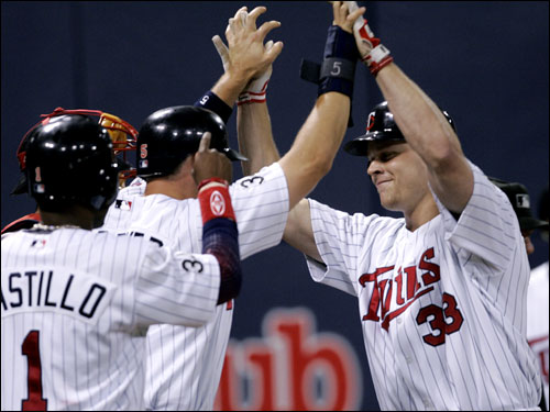 Justin Morneau, right, was welcomed at the plate by Michael Cuddyer and Luis Castillo after Morneau's grand slam.