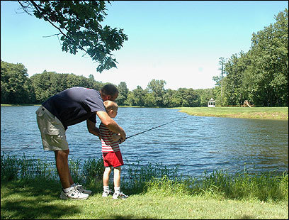 George Rimsky of New Jersey gives his son Nicolas, 5, some tips on fishing, while vacationing at the Sunny Hill Resort in Greenville, N.Y.
