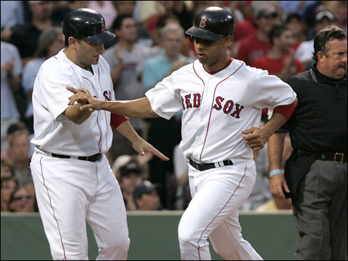 The single also scored Alex Cora (right), who celebrated with Doug Mirabelli after crossing the plate.