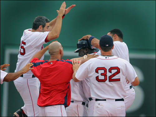 Mike Lowell (left), and Red Sox teammates surround David Ortiz after his game-winning single.
