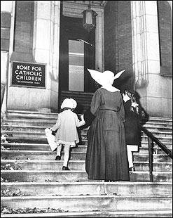 A nun escorted two girls into an orphanage that worked under the Catholic Charities Bureau. The home was a temporary site for orphans ages 3 to 12.