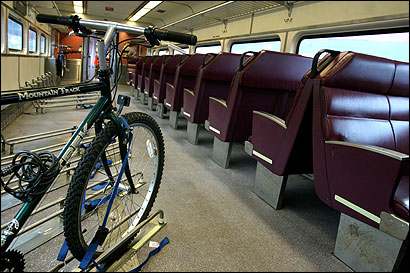 The MBTA unveiled yesterday a commuter rail coach fitted with 39 bicycle racks. Officials also toured the first coach completed in a $23.5 million program to refurbish air conditioning units and old windows in 162 commuter cars.