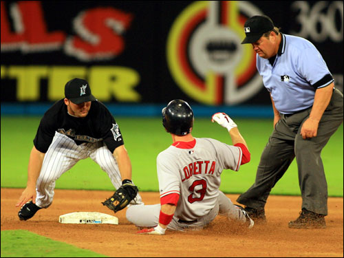 Marlins second baseman Dan Uggla, left, tagged out Mark Loretta on a single hit to deep left field in the fourth inning.