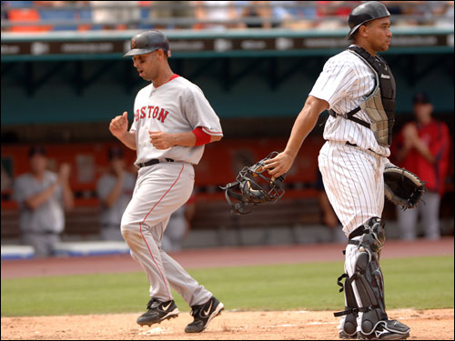 Alex Cora, left, scored the go-ahead run on a sacrifice fly by Mark Loretta in the eighth inning.