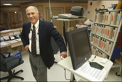 Dr. Daniel Shea stood next to the telemedicine monitor he uses to ''visit'' patients at New Bedford Health Care Center.