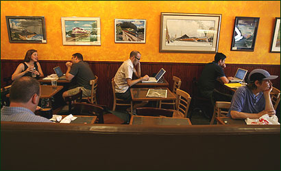 Dan Milstein, center, worked on his laptop at Emack & Bolio's in Jamaica Plain last week. Some say wireless cafes have become like offices.