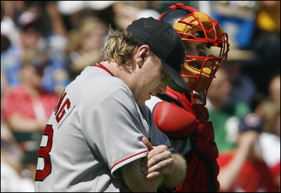 Curt Schilling rubbed his elbow while walking back to the mound with catcher Jason Varitek. The Red Sox starter was struck by a line drive in the sixth inning.