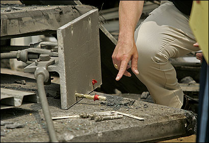 An FBI investigator pointed to an anchor bolt while investigating the debris in the tunnel yesterday.
