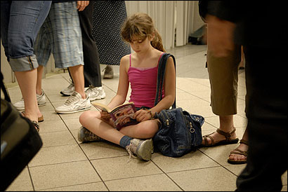 Stephanie Simonoff, 11, of Windham, N.H., read at North Station in Boston yesterday while waiting for her Lowell-bound train.