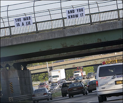Two antiwar signs posted on a Route 128 overpass in Weston lasted no more than 12 hours before being removed.