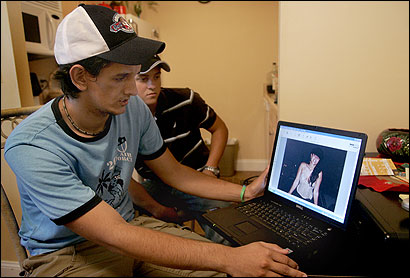Fausto DePaula (left), the brother of the woman who died after an illegal surgery, and Thibisun Rissari looked at a photograph of Fabiola DePaulo inside her Framingham apartment.