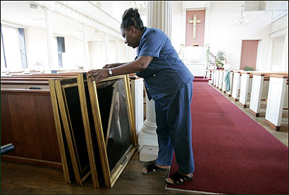 The Rev.Laurel Scott examined paintings that were slashed Thursday. Scott says she thinks more than one person was involved.