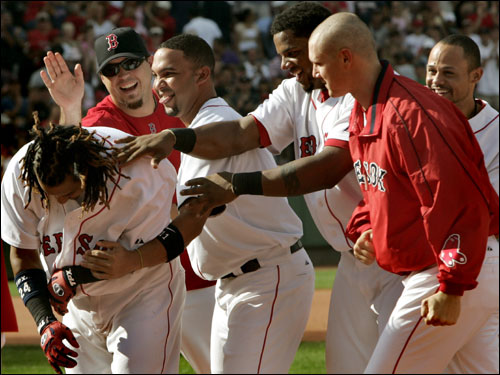 Red Sox players mobbed Manny Ramirez at first base after his walkoff single gave the Red Sox an 8-7 win.