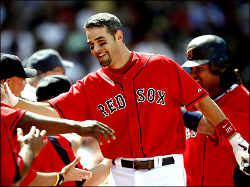 Mike Lowell was greeted in the dugout after Lowell's grand slam against the Orioles during the first inning.