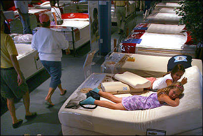 At Bernie & Phyl's furniture store in Braintree, Ashley Leone (foreground) and her sister, Jamie, of Pembroke, lay on a mattress while their parents looked at others.