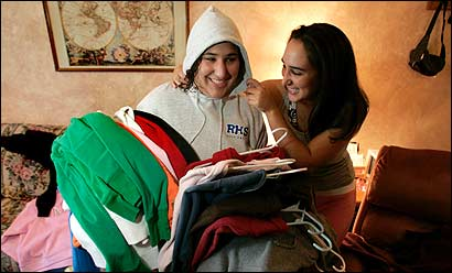 Randolph High School junior Darielle Grossman (left) and her older sister, Alanah, sorted through a pike of hooded sweatshirts that will soon be banned from school.