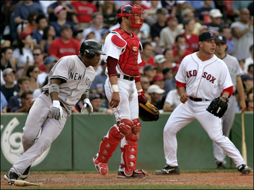 Robinson Cano (left) scored in the ninth inning on a single by Johnny Damon (not pictured) as Red Sox reliever Rudy Seanez (right) covered home.