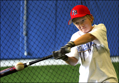 Zack O'Reilly, 12, of Plymouth practiced yesterday at the Frozen Ropes Training Center in Plymouth using an aluminum bat, which a joint legislative committee is considering banning.