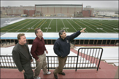 Lawrence Mayor Michael J. Sullivan (right) joins his chief of staff, Myles E. Burke (left), and planning director Michael Sweeney on a tour of a nearly complete Veterans Memorial Stadium.