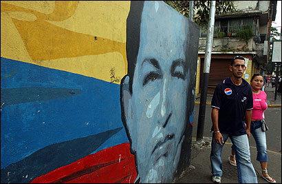 A couple passed by a mural of President Hugo Chávez in Caracas. Many murals of Chávez depicted alongside other revolutionary leaders have been painted around the Venezuelan capital, notably in poorer districts.