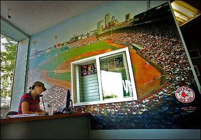 Natali Gingras worked next to a mural of a packed Fenway Park at Ace Ticket in Brookline yesterday. The Red Sox sellout streak is in jeopardy.