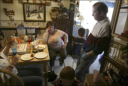 Larry Millette and his wife, Rose, visited by their grandchildren. Millette had once imagined a retirement in which he would spend more time with his grandchildren or travel with his wife, but those hopes were dashed by cuts in his pension plan.