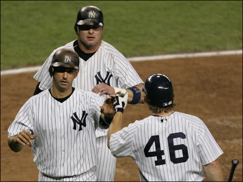 Aaron Guiel, right, greeted teammates Jorge Posada and Jason Giambi at the plate after the two scored on a double hit by Bernie Williams in the fourth inning.