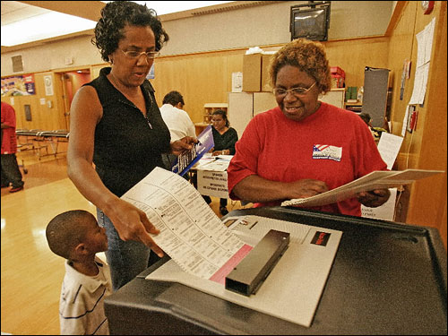 Voters across the state took to the polls Tuesday to vote on several races, including the Democratic candidate for governor. At left, Jenell Scott and her grandson, Jaylin Carty, 4, received help from election inspector Carol Stamper while casting her ballot at the Early Learning Center in Roxbury.